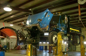 a large blue dump truck being worked on